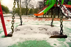 Empty swing in a park covered with melting snow Royalty Free Stock Photos