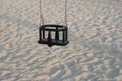 Empty Swing Seat for kids with white sand in background stock photo