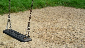 Empty swing seat swaying at playground in the park. Stock Photo