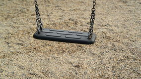 Empty swing seat swaying at playground in the park. Royalty Free Stock Photography