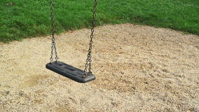 Empty swing seat swaying at playground in the park. Stock Photos