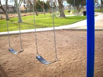 Empty swing set in park with blue posts. stock photography