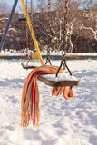 Empty swing with snow and checkered scarf Royalty Free Stock Image