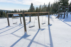 Empty swing with snow in winter Royalty Free Stock Image