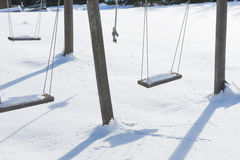 Empty swing with snow in winter Royalty Free Stock Photography