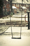 Empty swing with snow on it in the winter season Royalty Free Stock Images