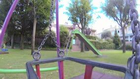 Empty Swing Swinging at Dusk Stock Photo