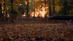 Empty swing swinging in slow motion during sun set stock footage
