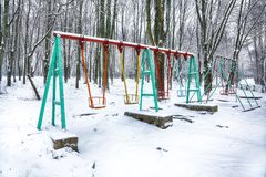 Empty swing in winter time with snow. Children`s swing under a thick layer of snow Stock Photo