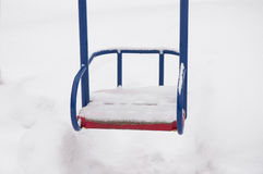 Empty swing in winter time with snow. Children's swing under a thick layer of snow Stock Images