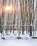Empty swing in winter time with snow. Children`s swing under a thick layer of snow Stock Photos