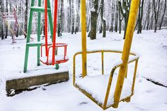 Empty swing in winter time with snow. Children`s swing under a thick layer of snow Royalty Free Stock Images