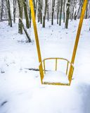 Empty swing in winter time with snow. Children`s swing under a thick layer of snow Stock Photography