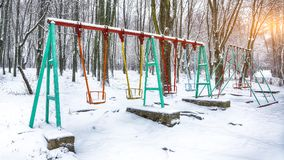 Empty swing in winter time with snow. Children`s swing under a thick layer of snow Royalty Free Stock Photos