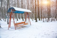 Empty swing in winter time with snow. Children`s swing under a thick layer of snow Stock Images