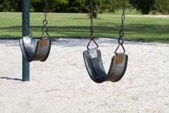 Empty Swings. In a vacant playground to be used as a conceptual image for abused, abducted or missing children Stock Photography