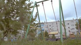 Empty swings on the background of homes slow motion video. Cloudy day empty swings sway on the background of homes slow motion video stock video