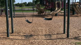 Empty Swings Going Back And Forth On Empty Playground stock footage
