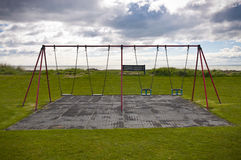 Empty swings on grass with sea and cloudy sky Royalty Free Stock Photo
