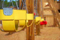 Empty Swings on Playground. Row of colorful children's swings on deserted playground Royalty Free Stock Photo