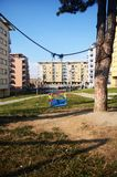 Empty swings in the playground. In front of building Stock Image