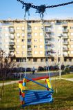 Empty swings in the playground. In front of building Royalty Free Stock Photo