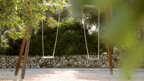 Empty swings in a playground stock footage