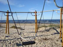 Empty swings on the sandy beach. Autumn Baltic seashore. stock image