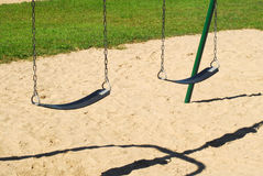 Empty swings on sandy playground Royalty Free Stock Photography