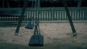 Empty swings swaying at playground stock footage