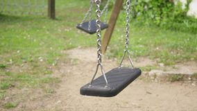 Empty Swings Swinging. Two empty swing swinging in the park stock footage