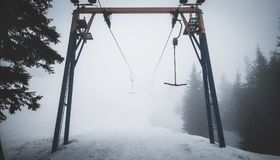 Empty t-bar lift in fog in mountains stock photography