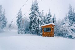 Empty t-bar lift and wooden building at snowfall stock photo