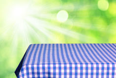 Empty table. With blue gingham tablecloth over green bokeh background. Great for product display montages Royalty Free Stock Images