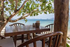 Empty table and chairs under trees on tropical beach. Beach cafe on seascape background. Outdoor restaurant wood furniture. Summer vacation concept. Travel in stock photo