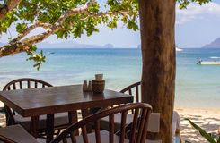 Empty table and chairs under trees on tropical beach. Beach cafe on seascape background. Outdoor restaurant wood furniture. Summer vacation concept. Travel in stock photography