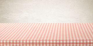Empty table cover with pink and white tablecloth over brown wall. Background, banner, table top, counter design for food and product display montage Stock Images