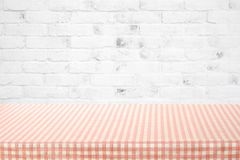 Empty table cover with pink and white tablecloth over white bric. K wall background, banner, table top, counter design for food and product display montage Stock Photo