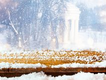 Empty table coverd with snow in front of dreamy and magical winter landscape background. For product display montage. Empty wooden table coverd with snow in Royalty Free Stock Photo
