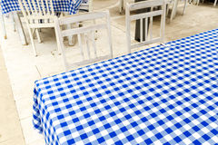 Empty table covered with blue and white chequered tablecloth nex Royalty Free Stock Image