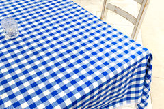 Empty table covered with blue and white chequered tablecloth nex Royalty Free Stock Photo