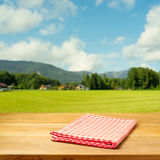Empty table covered with checked tablecloth over beautiful landscape Royalty Free Stock Photo