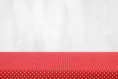 Empty table covered with red polka dot tablecloth over white cement wall background