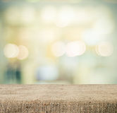 Empty table covered with sackcloth over blurred abstract background with bokeh Stock Images
