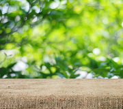 Empty table covered with sackcloth over blurred trees with bokeh background Stock Image