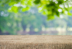 Empty table covered with sackcloth over blurred trees with bokeh Royalty Free Stock Photo