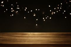 Empty table in front of black and gold glitter garland lights background Royalty Free Stock Photo