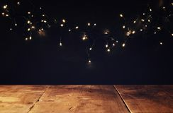 Empty table in front of black and gold glitter garland lights background Stock Image