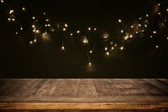 Empty table in front of black and gold glitter garland lights background Stock Photo