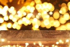 Empty table in front of black and gold glitter lights background. For product display montage Royalty Free Stock Photo